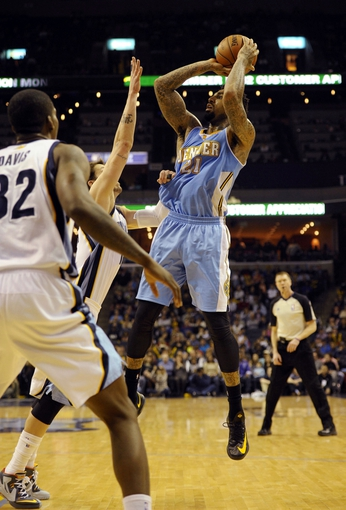 Dec 28, 2013; Memphis, TN, USA; Denver Nuggets small forward Wilson Chandler (21) handles the ball against Memphis Grizzlies small forward Mike Miller (13) during the fourth quarter at FedExForum. Mandatory Credit: Justin Ford-USA TODAY Sports