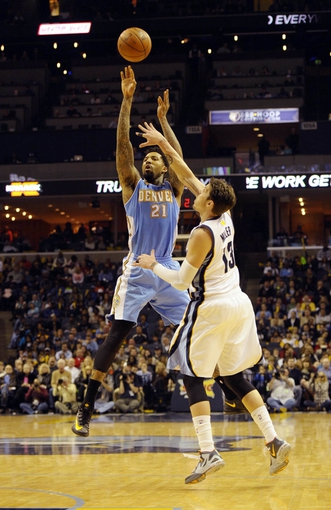 Dec 28, 2013; Memphis, TN, USA; Denver Nuggets small forward Wilson Chandler (21) shoots over Memphis Grizzlies small forward Mike Miller (13) during the fourth quarter at FedExForum. Memphis Grizzlies beat the Denver Nuggets 120-99. Mandatory Credit: Justin Ford-USA TODAY Sports