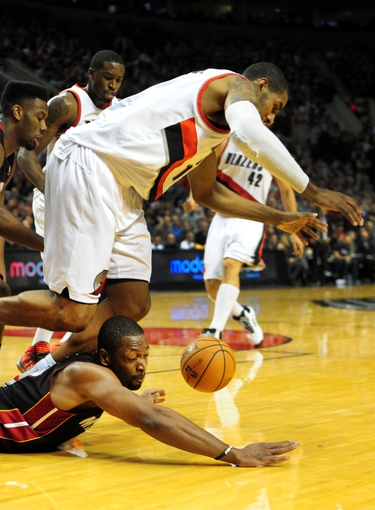 Dec 28, 2013; Portland, OR, USA; Miami Heat shooting guard Dwyane Wade (3) and Portland Trail Blazers power forward LaMarcus Aldridge (12) scramble for a loose ball during the fourth quarter of the game at the Moda Center.
