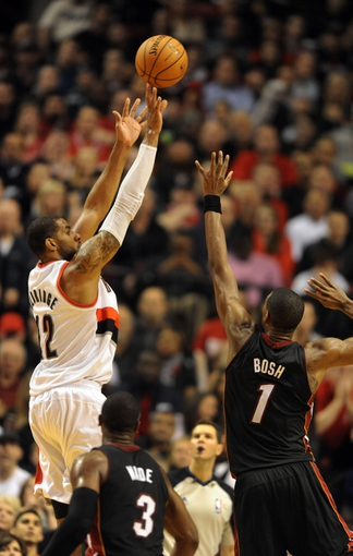 Dec 28, 2013; Portland, OR, USA; Portland Trail Blazers power forward LaMarcus Aldridge (12) hits a shot over Miami Heat shooting guard Dwyane Wade (3) and center Chris Bosh (1) during the fourth quarter of the game at the Moda Center. The Heat won the game 108-107. Mandatory Credit: Steve Dykes-USA TODAY Sports