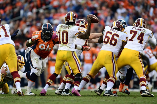Oct 27, 2013; Denver, CO, USA; Denver Broncos defensive tackle Terrance Knighton (94) hurries Washington Redskins quarterback Robert Griffin III (10) in the fourth quarter at Sports Authority Field at Mile High. Mandatory Credit: Ron Chenoy-USA TODAY Sports