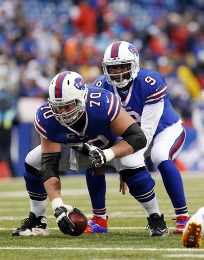Dec 22, 2013; Orchard Park, NY, USA; Buffalo Bills center Eric Wood (70) snaps the ball to quarterback Thad Lewis (9) during the second half at Ralph Wilson Stadium. Bills beat the Dolphins 19-0. Mandatory Credit: Kevin Hoffman-USA TODAY Sports
