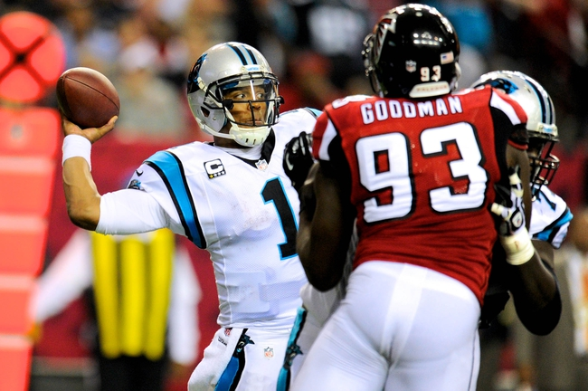 Dec 29, 2013; Atlanta, GA, USA; Carolina Panthers quarterback Cam Newton (1) passes the ball under pressure against the Atlanta Falcons during the second half at the Georgia Dome. The Panthers defeated the Falcons 21-20. Mandatory Credit: Dale Zanine-USA TODAY Sports