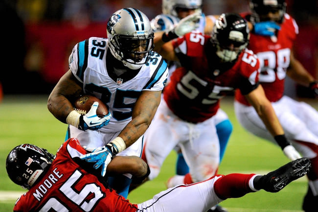 Dec 29, 2013; Atlanta, GA, USA; Carolina Panthers fullback Mike Tolbert (35) breaks a tackle by Atlanta Falcons safety William Moore (25) during the second half at the Georgia Dome. The Panthers defeated the Falcons 21-20. Mandatory Credit: Dale Zanine-USA TODAY Sports