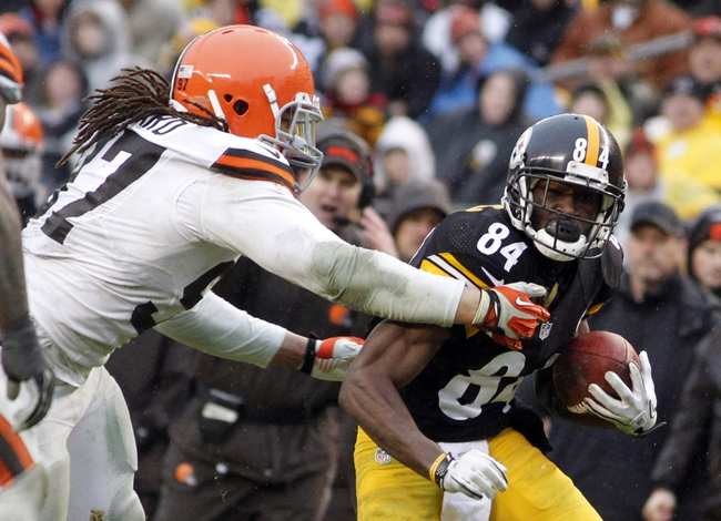 Dec 29, 2013; Pittsburgh, PA, USA; Pittsburgh Steelers wide receiver Antonio Brown (84) runs after a pass reception as Cleveland Browns outside linebacker Jabaal Sheard (97) defends during the fourth quarter at Heinz Field. The Pittsburgh Steelers won 20-7. Mandatory Credit: Charles LeClaire-USA TODAY Sports