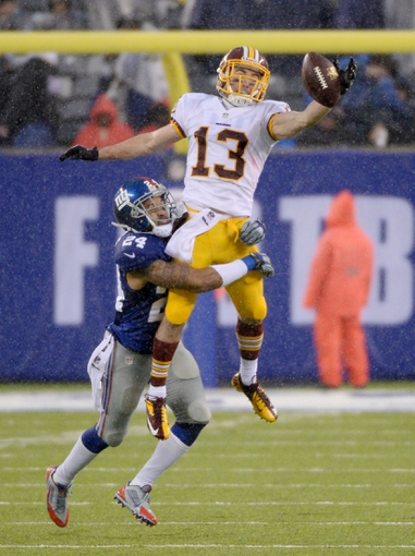 Dec 29, 2013; East Rutherford, NJ, USA; Washington Redskins wide receiver Nick Williams (13) cannot catch a pass while defended by New York Giants cornerback Terrell Thomas (24) during the game at MetLife Stadium. Mandatory Credit: Robert Deutsch-USA TODAY Sports