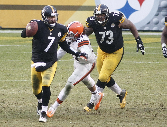 Dec 29, 2013; Pittsburgh, PA, USA; Pittsburgh Steelers quarterback Ben Roethlisberger (7) scrambles with the ball as Cleveland Browns outside linebacker Jabaal Sheard (97) pursues during the fourth quarter at Heinz Field. The Pittsburgh Steelers won 20-7. Mandatory Credit: Charles LeClaire-USA TODAY Sports