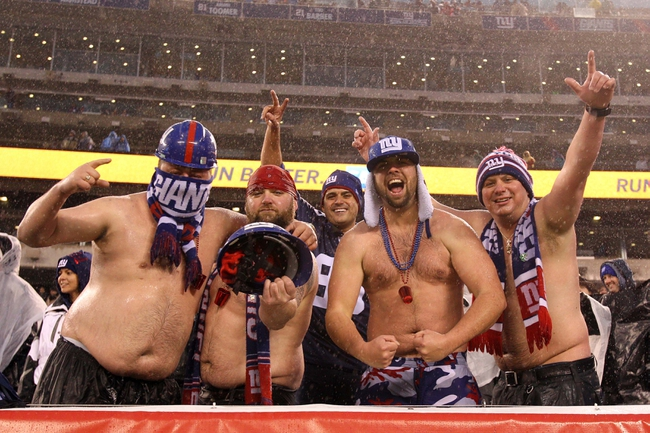 Dec 29, 2013; East Rutherford, NJ, USA;  New York Giants fans cheer in the rain during the game against the Washington Redskins at MetLife Stadium. The Giants defeated the Redskins 20-6. Mandatory Credit: Brad Penner-USA TODAY Sports
