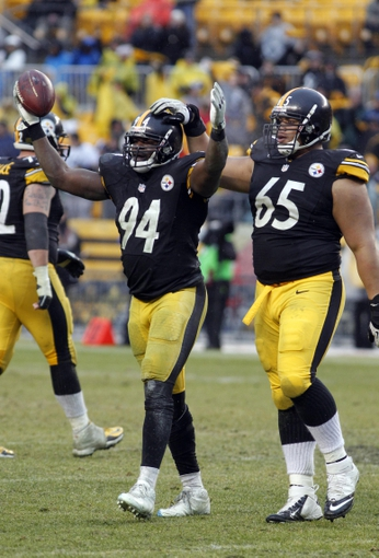 Dec 29, 2013; Pittsburgh, PA, USA; Pittsburgh Steelers inside linebacker Lawrence Timmons (94) celebrates his interception as nose tackle Al Woods (65) congratulates Timmons against the Cleveland Browns during the fourth quarter at Heinz Field. The Pittsburgh Steelers won 20-7. Mandatory Credit: Charles LeClaire-USA TODAY Sports