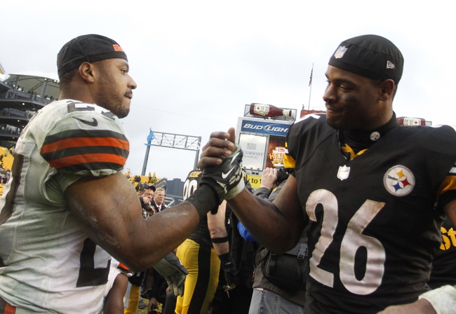 Dec 29, 2013; Pittsburgh, PA, USA; Cleveland Browns running back Edwin Baker (left) and Pittsburgh Steelers running back Le'Veon Bell (26) meet at mid-field after playing at Heinz Field. The Pittsburgh Steelers won 20-7. Mandatory Credit: Charles LeClaire-USA TODAY Sports