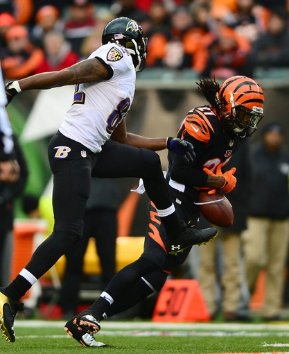 Dec 29, 2013; Cincinnati, OH, USA; Cincinnati Bengals cornerback Dre Kirkpatrick (27) intercepts a pass intended for Baltimore Ravens wide receiver Torrey Smith (82) during the fourth quarter at Paul Brown Stadium. Bengals defeated the Ravens 34-17. Mandatory Credit: Andrew Weber-USA TODAY Sports