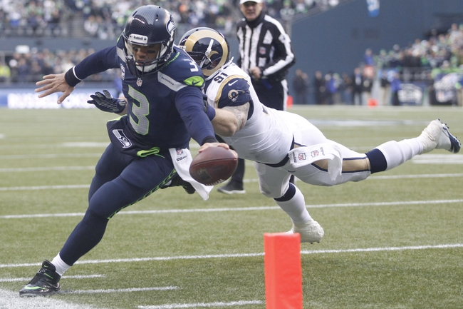 Dec 29, 2013; Seattle, WA, USA; Seattle Seahawks quarterback Russell Wilson (3) runs with the ball against the St. Louis Rams during the third quarter at CenturyLink Field. Mandatory Credit: Joe Nicholson-USA TODAY Sports