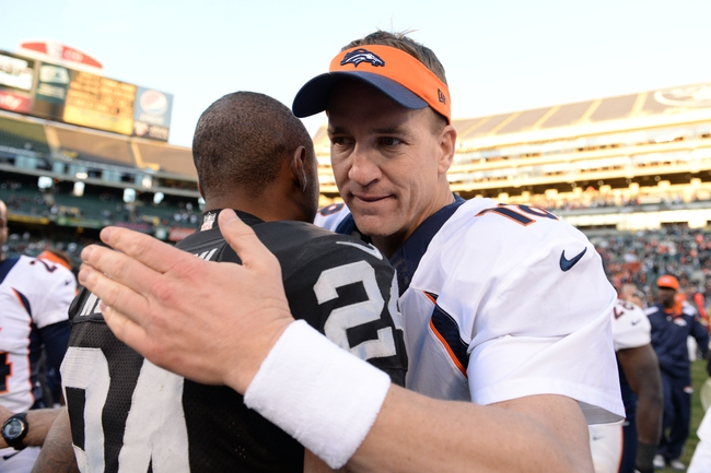 December 29, 2013; Oakland, CA, USA; Denver Broncos quarterback Peyton Manning (18, right) shakes hands with Oakland Raiders free safety Charles Woodson (24) at O.co Coliseum. The Broncos defeated the Raiders 34-14. Mandatory Credit: Kyle Terada-USA TODAY Sports
