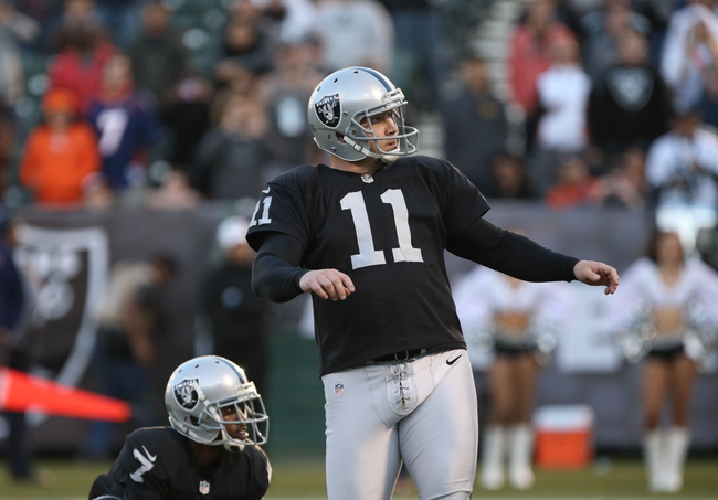 Dec 29, 2013; Oakland, CA, USA; Oakland Raiders kicker Sebastian Janikowski (11) kicks an extra point against the Denver Broncos during the fourth quarter at O.co Coliseum. The Denver Broncos defeated the Oakland Raiders 34-14. Mandatory Credit: Kelley L Cox-USA TODAY Sports
