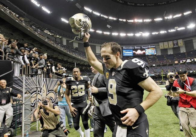Dec 29, 2013; New Orleans, LA, USA; New Orleans Saints quarterback Drew Brees (9) holds his helmet up to fans as he leaves the field at the Mercedes-Benz Superdome. New Orleans defeated the Tampa Bay Buccaneers 42-17. Mandatory Credit: Crystal LoGiudice-USA TODAY Sports
