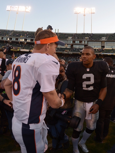 Dec 29, 2013; Oakland, CA, USA; Denver Broncos quarterback Peyton Manning (18) shakes hands with Oakland Raiders quarterback Terrelle Pryor (2) after the game at O.co Coliseum. The Broncos won 34-14. Mandatory Credit: Kirby Lee-USA TODAY Sports