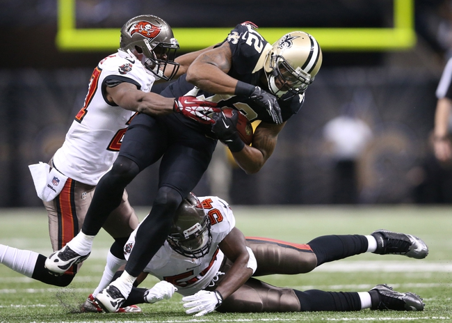 Dec 29, 2013; New Orleans, LA, USA; New Orleans Saints wide receiver Marques Colston (12) is tackled by Tampa Bay Buccaneers cornerback Johnthan Banks (27) and outside linebacker Lavonte David (54) in the second half at the Mercedes-Benz Superdome. New Orleans defeated Tampa Bay 42-17. Mandatory Credit: Crystal LoGiudice-USA TODAY Sports