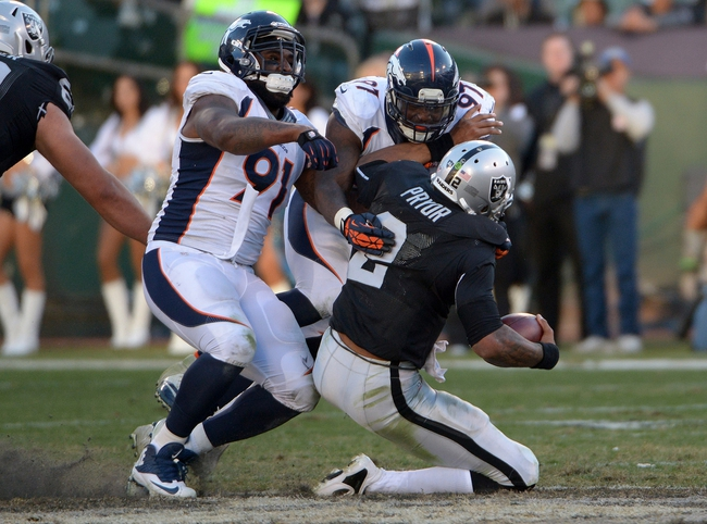Dec 29, 2013; Oakland, CA, USA; Oakland Raiders quarterback Terrelle Pryor (2) is sacked by Denver Broncos defensive ends Malik Jackson (97) and Robert Ayers (91) at O.co Coliseum. The Broncos won 34-14. Mandatory Credit: Kirby Lee-USA TODAY Sports