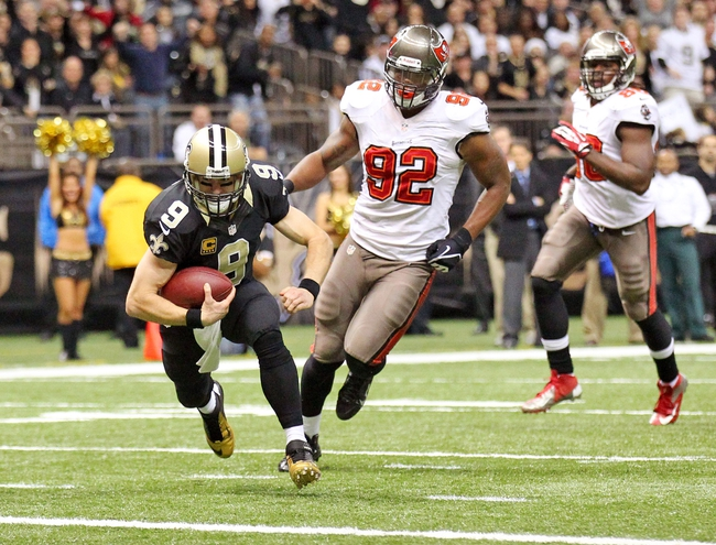 Dec 29, 2013; New Orleans, LA, USA; New Orleans Saints quarterback Drew Brees (9) carries the ball in front of Tampa Bay Buccaneers defensive end William Gholston (92) for a touchdown in the second half at the Mercedes-Benz Superdome. New Orleans defeated Tampa Bay 42-17. Mandatory Credit: Crystal LoGiudice-USA TODAY Sports