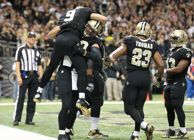 Dec 29, 2013; New Orleans, LA, USA; New Orleans Saints quarterback Drew Brees (9) is lifted up by tight end Jimmy Graham (80) after a touchdown against the Tampa Bay Buccaneers in the second half at the Mercedes-Benz Superdome. New Orleans defeated Tampa Bay 42-17. Mandatory Credit: Crystal LoGiudice-USA TODAY Sports