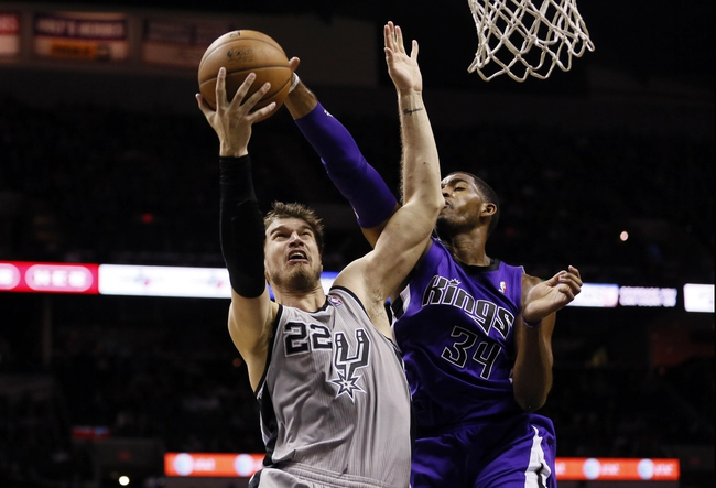 Dec 29, 2013; San Antonio, TX, USA; San Antonio Spurs forward Tiago Splitter (22) drives to the basket under pressure from Sacramento Kings forward Jason Thompson (34) during the first half at the AT&T Center. Mandatory Credit: Soobum Im-USA TODAY Sports