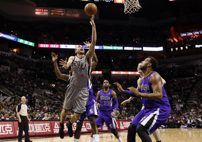 Dec 29, 2013; San Antonio, TX, USA; San Antonio Spurs guard Manu Ginobili (20) drives to the basket as Sacramento Kings forward Derrick Williams (right) looks on during the first half at the AT&T Center. Mandatory Credit: Soobum Im-USA TODAY Sports