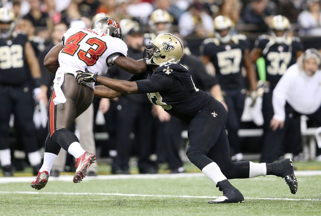 Dec 29, 2013; New Orleans, LA, USA; New Orleans Saints outside linebacker Junior Galette (93) reaches to tackle Tampa Bay Buccaneers running back Bobby Rainey (43) in the second half at the Mercedes-Benz Superdome. New Orleans defeated Tampa Bay 42-17. Mandatory Credit: Crystal LoGiudice-USA TODAY Sports