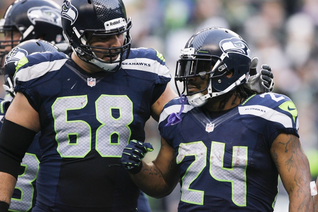 Dec 29, 2013; Seattle, WA, USA; Seattle Seahawks running back Marshawn Lynch (24) celebrates a touchdown run with Seattle Seahawks tackle Breno Giacomini (68) during the third quarter at CenturyLink Field. Mandatory Credit: Joe Nicholson-USA TODAY Sports