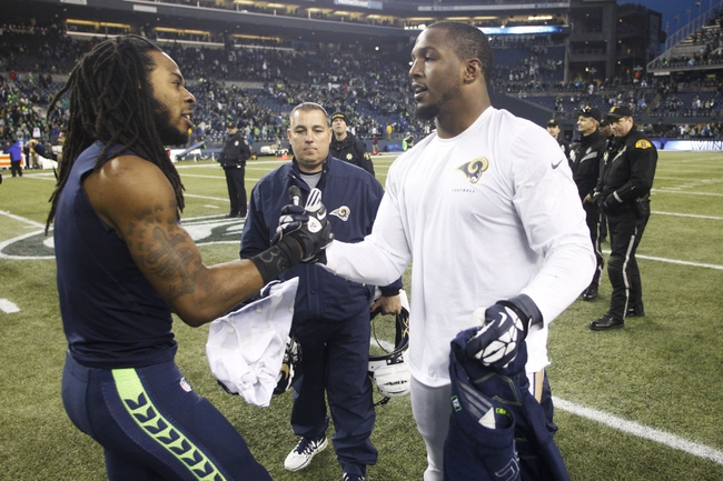 Dec 29, 2013; Seattle, WA, USA; Seattle Seahawks cornerback Richard Sherman (25) exchanges jerseys with St. Louis Rams defensive end Robert Quinn (94) following a 29-7 Seattle Seahawks victory at CenturyLink Field. Mandatory Credit: Joe Nicholson-USA TODAY Sports