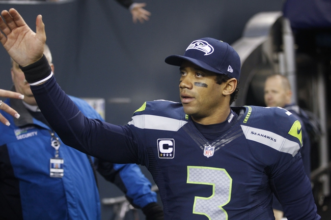 Dec 29, 2013; Seattle, WA, USA; Seattle Seahawks quarterback Russell Wilson (3) high-fives fans following a 29-7 victory against the St. Louis Rams at CenturyLink Field. Mandatory Credit: Joe Nicholson-USA TODAY Sports