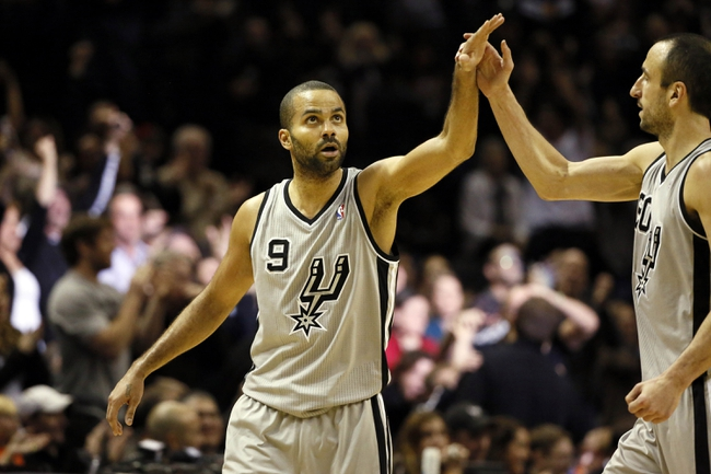 Dec 29, 2013; San Antonio, TX, USA; San Antonio Spurs guard Tony Parker (9) celebrates a score with Manu Ginobili (right) during the second half against the Sacramento Kings at the AT&T Center. The Spurs won 112-104. Mandatory Credit: Soobum Im-USA TODAY Sports