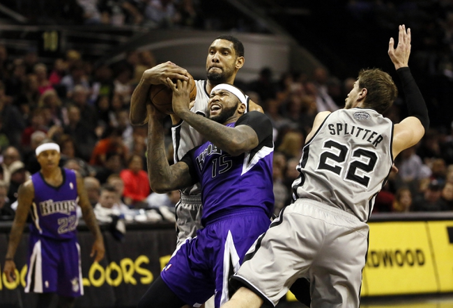 Dec 29, 2013; San Antonio, TX, USA; San Antonio Spurs forward Tim Duncan (21) ties up Sacramento Kings center DeMarcus Cousins (15) as he drives to the basket during the second half at the AT&T Center. The Spurs won 112-104. Mandatory Credit: Soobum Im-USA TODAY Sports
