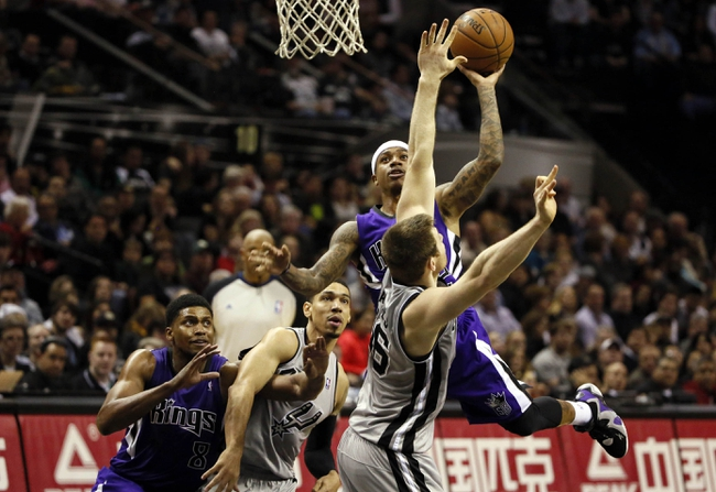 Dec 29, 2013; San Antonio, TX, USA; Sacramento Kings guard Isaiah Thomas (top) drives to the basket as San Antonio Spurs forward Aron Baynes (bottom) defends during the second half at the AT&T Center. The Spurs won 112-104. Mandatory Credit: Soobum Im-USA TODAY Sports
