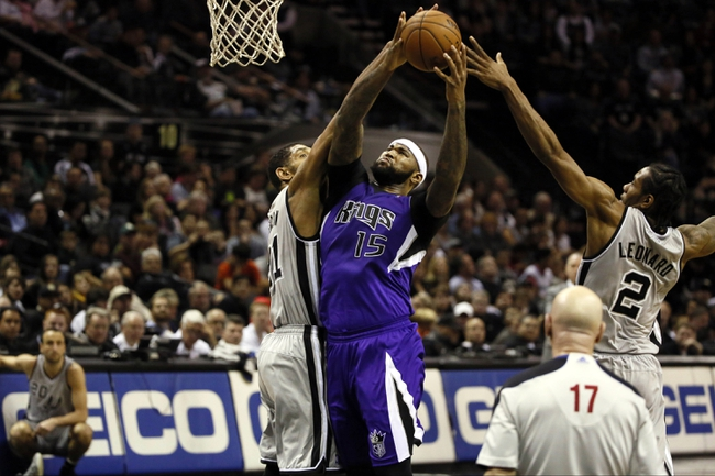 Dec 29, 2013; San Antonio, TX, USA; Sacramento Kings center DeMarcus Cousins (15) drives for the basket between San Antonio Spurs forward Tim Duncan (left) and Kawhi Leonard (right) during the second half at the AT&T Center. The Spurs won 112-104. Mandatory Credit: Soobum Im-USA TODAY Sports