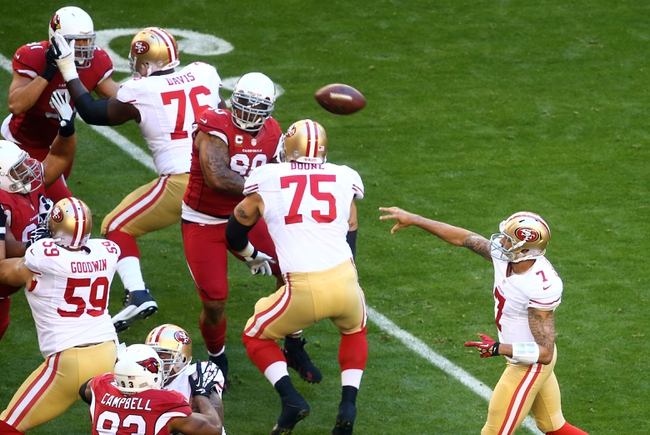 Dec 29, 2013; Phoenix, AZ, USA; San Francisco 49ers quarterback Colin Kaepernick (7) throws a pass against the Arizons Cardinals at University of Phoenix Stadium. Mandatory Credit: Mark J. Rebilas-USA TODAY Sports