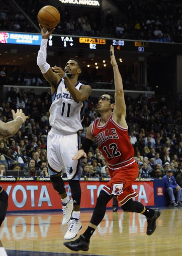 Dec 30, 2013; Memphis, TN, USA; Memphis Grizzlies point guard Mike Conley (11) shoots the ball as Chicago Bulls shooting guard Kirk Hinrich (12) defends during the fourth quarter at FedExForum. The Bulls won 95 - 91. Mandatory Credit: Justin Ford-USA TODAY Sports