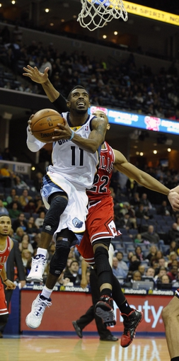 Dec 30, 2013; Memphis, TN, USA; Memphis Grizzlies point guard Mike Conley (11) shoots the ball in front of Chicago Bulls power forward Taj Gibson (22) during the fourth quarter at FedExForum. The Bulls won 95 - 91. Mandatory Credit: Justin Ford-USA TODAY Sports