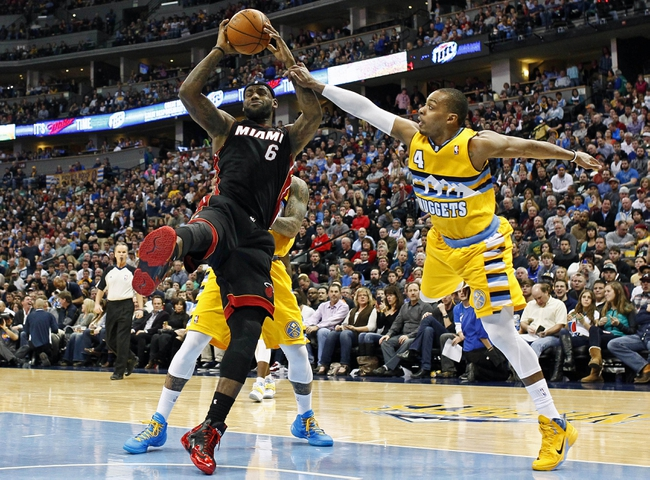 Dec 30, 2013; Denver, CO, USA; Denver Nuggets point guard Randy Foye (4) fouls Miami Heat small forward LeBron James (6) in the third quarter at the Pepsi Center. The Heat defeated the Nuggets 97-94. Mandatory Credit: Isaiah J. Downing-USA TODAY Sports