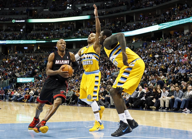 Dec 30, 2013; Denver, CO, USA; Miami Heat shooting guard Ray Allen (34) drives to the net against Denver Nuggets point guard Randy Foye (4) and power forward J.J. Hickson (7) in the third quarter at the Pepsi Center. The Heat defeated the Nuggets 97-94. Mandatory Credit: Isaiah J. Downing-USA TODAY Sports