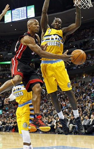 Dec 30, 2013; Denver, CO, USA; Miami Heat shooting guard Ray Allen (34) passes the ball around Denver Nuggets power forward J.J. Hickson (7) in the third quarter at the Pepsi Center. The Heat defeated the Nuggets 97-94. Mandatory Credit: Isaiah J. Downing-USA TODAY Sports