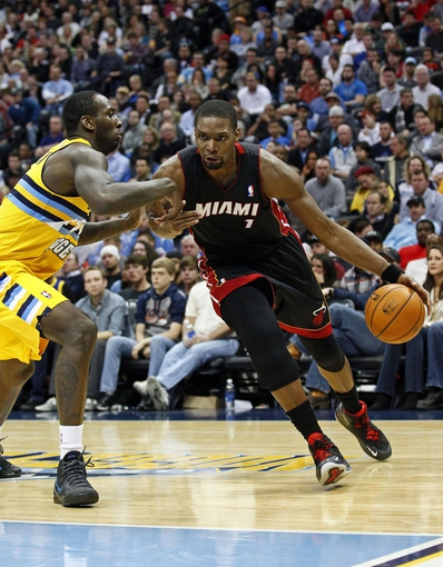 Dec 30, 2013; Denver, CO, USA; Denver Nuggets power forward J.J. Hickson (7) guards Miami Heat center Chris Bosh (1) in the fourth quarter at the Pepsi Center. The Heat defeated the Nuggets 97-94. Mandatory Credit: Isaiah J. Downing-USA TODAY Sports