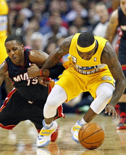 Dec 30, 2013; Denver, CO, USA; Denver Nuggets point guard Ty Lawson (3) gets tied up with Miami Heat point guard Mario Chalmers (15) in the fourth quarter at the Pepsi Center. The Heat defeated the Nuggets 97-94. Mandatory Credit: Isaiah J. Downing-USA TODAY Sports