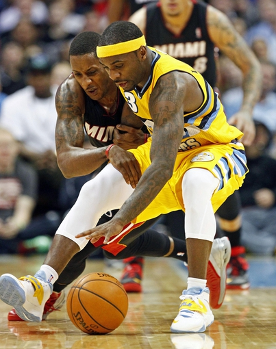 Dec 30, 2013; Denver, CO, USA; Miami Heat point guard Mario Chalmers (15) and Denver Nuggets point guard Ty Lawson (3) battle for the ball in the fourth quarter at the Pepsi Center. The Heat defeated the Nuggets 97-94. Mandatory Credit: Isaiah J. Downing-USA TODAY Sports