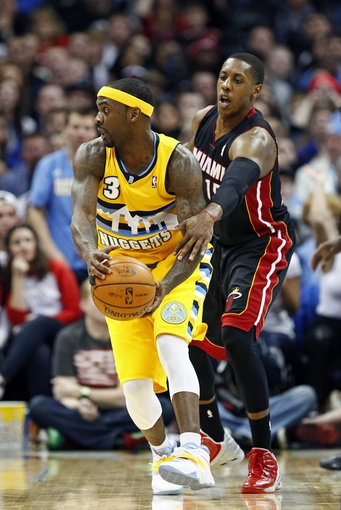 Dec 30, 2013; Denver, CO, USA; Miami Heat point guard Mario Chalmers (15) fouls Denver Nuggets point guard Ty Lawson (3) in the fourth quarter at the Pepsi Center. The Heat defeated the Nuggets 97-94. Mandatory Credit: Isaiah J. Downing-USA TODAY Sports