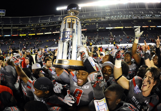 Dec 30, 2013; San Diego, CA, USA; Texas Tech Red Raiders players celebrate with the Holiday Bowl trophy after a win against the Arizona State Sun Devils at Qualcomm Stadium. Texas Tech won 37-23. Mandatory Credit: Christopher Hanewinckel-USA TODAY Sports
