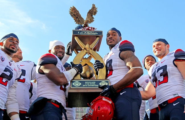 Dec 31, 2013; Shreveport, LA, USA; Arizona Wildcats running back Daniel Jenkins (3) and wide receiver Terrence Miller (18) and teammates hold up the trophy as they celebrate defeating the Boston College Eagles 42-19 at Independence Stadium. Mandatory Credit: Crystal LoGiudice-USA TODAY Sports
