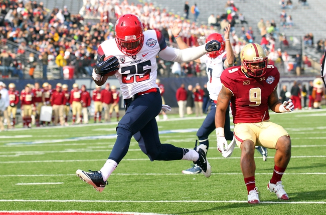 Dec 31, 2013; Shreveport, LA, USA; Arizona Wildcats running back Ka'Deem Carey (25) carries the ball into the end zone for a touchdown in front of Boston College Eagles defensive back Dominique Williams (9) in the third quarter at Independence Stadium. Arizona defeated Boston College 42-19. Mandatory Credit: Crystal LoGiudice-USA TODAY Sports