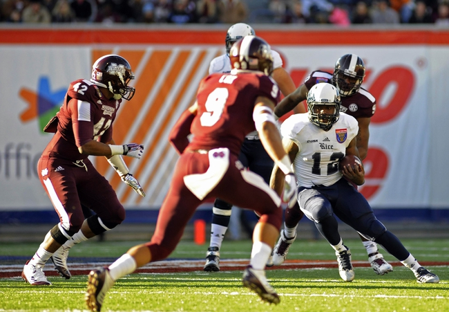 Dec 31, 2013; Memphis, TN, USA; Rice Owls running back Charles Ross (12) carries the ball against Mississippi State Bulldogs linebacker Beniquez Brown (42) and defensive back Justin Cox (9) during the first quarter at Liberty Bowl Memorial Stadium. Mandatory Credit: Justin Ford-USA TODAY Sports