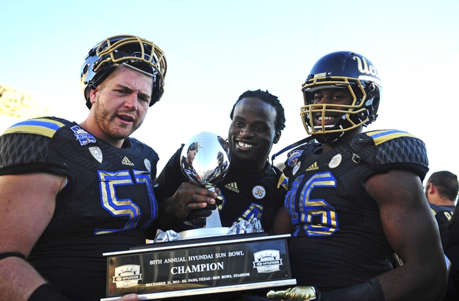 Dec 31, 2013; El Paso, TX, USA; UCLA Bruins center Carl Hulick (57) and defensive end Owamagbe Odighizuwa (94) and linebacker Kenny Orjioke (46) hold the 2013 Sun Bowl trophy at Sun Bowl Stadium. UCLA defeated Virginia Tech 42-12. Mandatory Credit: Andrew Weber-USA TODAY Sports