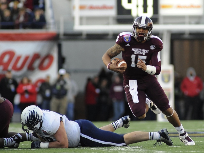 Dec 31, 2013; Memphis, TN, USA; Mississippi State Bulldogs quarterback Dak Prescott (15) carries the ball against the Rice Owls during the second quarter at Liberty Bowl Memorial Stadium. Mandatory Credit: Justin Ford-USA TODAY Sports